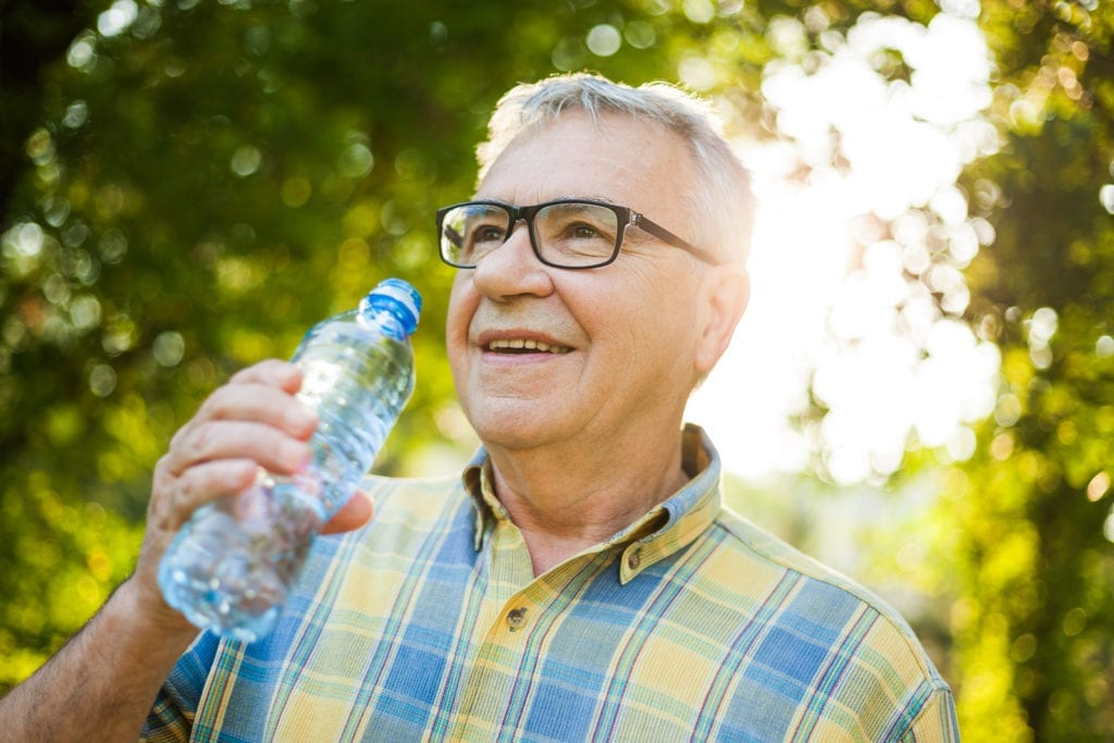 Senior man enjoying the benefits of drinking water on a hot summer day