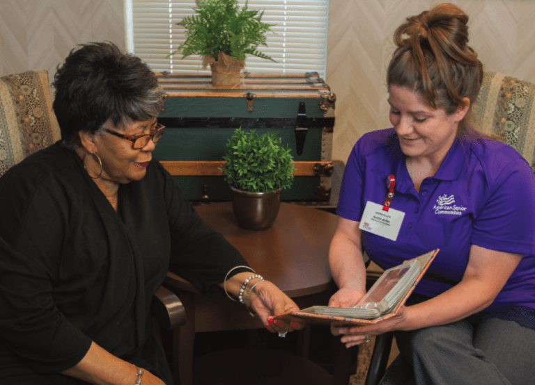 a caregiver and resident looking at a photo album